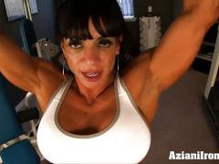 Bodybuilder flexes her muscles and strips in the gym