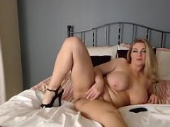Hot blonde woman strips and fingers her pussy