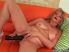Grandmother with large breasts pushes huge dildo inside